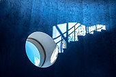 Round window and shadow of stairs with railing on blue wall