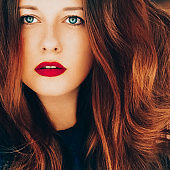 Beautiful redhead woman, red lipstick makeup look and wavy long hairstyle, beauty portrait and hair care