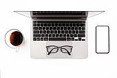 White office desk table with laptop computer, smartphone with blank mockup screen and cup of coffee, top view image flat layout.