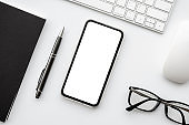 Smartphone with blank mockup screen is on top of white office desk table with supplies. Top view with copy space, flat lay.