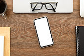 Smartphone with blank mockup screen is on top of wood office desk table with supplies. Top view with copy space, flat lay.