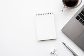 Small blank notebook is on top of white office desk table with laptop computer, cup of coffee and office supplies. Top view with copy space, flat lay.