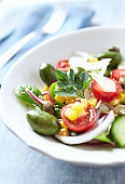 Healthy Salad with Green Olives, Baby Spinach, Cucumber, Cherry Tomatoes and Capers. Bright wooden background. Close up.