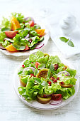 Salad with red and yellow Tomatoes and Pomegranate Seeds on bright wooden Background. Healthy Snack Idea.
