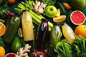 Fresh fruit and vegetable smoothies or juice in bottles with various ingredients around