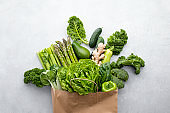 A paper shopping bag full of fresh leafy greens and vegetables
