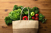 A textile reusable shopping bag full of fresh leafy greens and vegetables