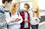 Group of teen students wearing face masks in London - Multiracial group of teenagers best friends enjoying time together in London during coronavirus  - Lifestyle and friendship in London