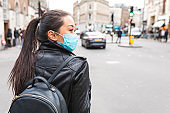 Chinese woman in London wearing anti coronavirus face mask while on essential travel during lockdown - health and lifestyle concepts