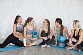 Attractive young sport women are having rest after doing yoga together.