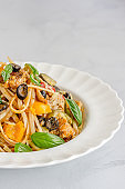 Summer Pasta with Chicken and Veggies on White Background Vertical Photo