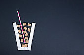 Glass with straw full of sugar cubes - unhealthy diet concept.