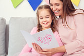 Mother and daughter together at home celebration concept sitting reading greeting card