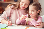 Mother and daughter weekend together at home education concept sitting at the table hugging drawing