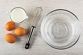 Pitcher with milk, brown eggs, whisk, empty bowl on wooden table. Top view