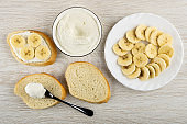 Spoon on slice of bread, sandwich with cottage cheese and banana, bowl with soft cottage cheese, plate with slices of banana on table. Top view