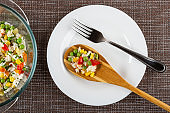 Vegetable blend in transparent bowl, bamboo spoon with vegetable blend and fork in plate on mat. Top view