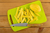 Peeled potato, knife, slices of potato on cutting board on wooden table. Top view