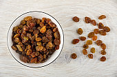 Dried grape in bowl, raisin on wooden table. Top view