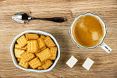 Spoon, light-blue bowl with salted crackers, cup of coffee, sugar cubes on wooden table. Top view