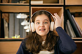 Little girl wearing headphones during online education course, lesson, view of screen