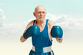 Senior man wearing sportwear boxing on sky background. Concept of sport, activity, movement, wellbeing. Copyspace, ad.