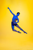 Young and graceful ballet dancer isolated on yellow studio background in neon light. Art, motion, action, flexibility, inspiration concept.