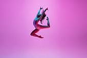 Young and graceful ballet dancer isolated on pink studio background in neon light. Art, motion, action, flexibility, inspiration concept.