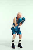 Senior man wearing sportwear boxing isolated on studio background. Concept of sport, activity, movement, wellbeing. Copyspace, ad.