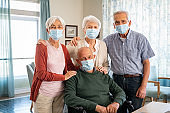 Group of happy senior people with face mask smiling at nursing home