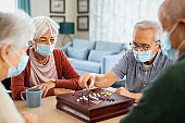 Senior friends playing chinese checkers at nursing home