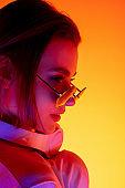 Caucasian woman's portrait isolated on orange studio background in multicolored neon light