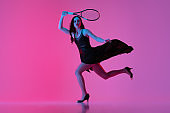 High-fashion styled young woman in black evening gown, dress playing tennis isolated over pink neon background. Concept of fashion and sport