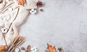 Autumn composition. A cup of coffee, cotton flowers, autumn leaves and sweater on stone background. Flat lay, top view with copy space.