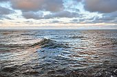 Panoramic view of the open Baltic sea at sunset. Dramatic sky with colorful glowing cumulus clouds. Water surface texture close-up. Fickle weather, winter, climate change, ocean swell, nature