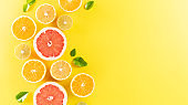 Summer composition made from oranges, lemon or lime on pastel yellow background. Fruit minimal concept. Flat lay, top view, copy space.