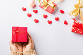 Woman hands holding gift or present box decorated and red heart surprise