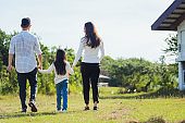 Asian family having fun and enjoying outdoor walking down the road outside together in the park