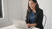 businesswoman video call with friends at home by laptop