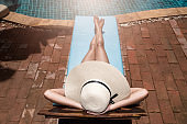 Asian young Women relaxing sleep poolside at luxury swimming pool