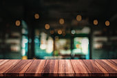 Empty of wood table with blur cafe or coffee shop background.