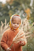 Cute beautiful girl in a yellow scarf in an autumn park with tall grass