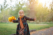 Little girl in a warm autumn coat walks, runs, whirls in the park with a bouquet of yellow maple leaves.