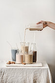 Human hand pouring fresh almond dairy free milk from bottle