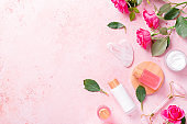 Rose extract natural cosmetics in refillable bottles with gua sha facial beauty roller and natural rose flowers on pink