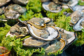 Street food market in Asia. Fresh oysters on the open-air fish counter