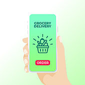 """A hand holding smart phone that shows grocery basket and """"order"""" button."""