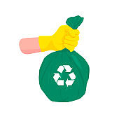 Hand was wearing yellow gloves and was carrying a green recycle garbage bag.