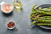 Asparagus. Fresh green asparagus bunch ready for cooking on gray slate stone table background. Top view copy space.