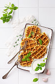 Homemade zucchini waffles with cheese,sause and leaf basil on white background. Concept of keto diet food. Selective focus.